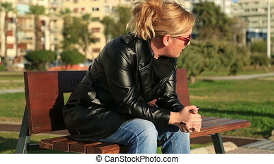 Worried woman sitting on a park - Sad blonde woman on the...