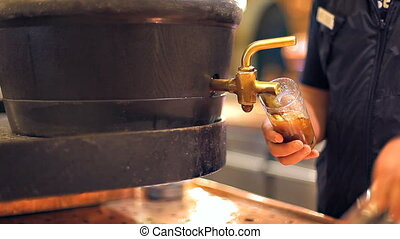 A bartender is pouring a dark beer - A close-up of hands,...