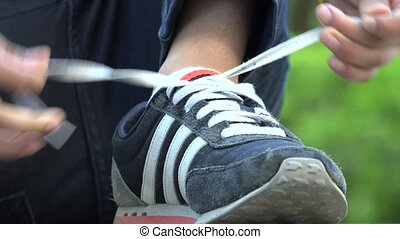 Young Boy Tying His Shoes