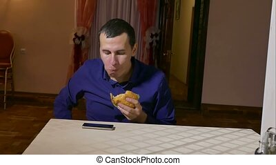 man eating hamburger food fast food sitting in the cafe -...