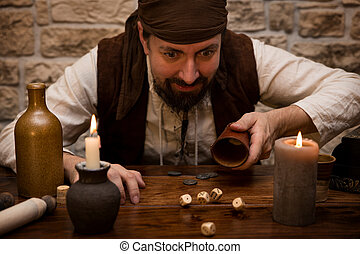 Pirate is gambling with dice on a medieval table, concept...