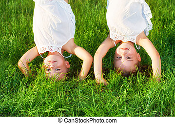 happy children twins sister upside down in summer