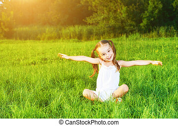 happy child little girl spread his arms in  white dress lying on Summer
