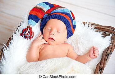 Cute newborn baby in blue knit cap sleeping in basket