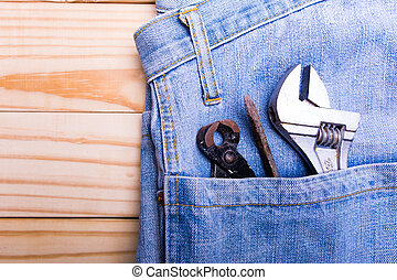 pliers and screw driver and wrench in jean on wooden background