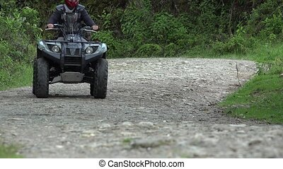 Man Driving ATV on Dirt Road