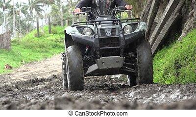 Man Driving ATV Through Mud