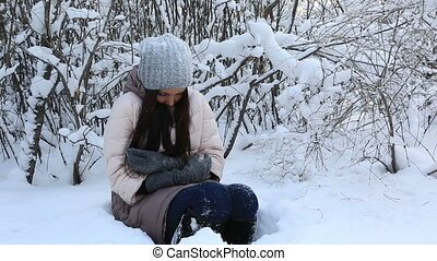 Beautiful poor girl has frozen in snowdrift under the snow covered tree.
