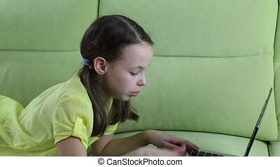 Beautiful little girl talking and typing on laptop -...