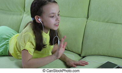Beautiful emotional girl listening to song on laptop and...