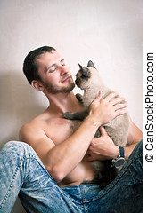 Young man sitting on the floor with his cat