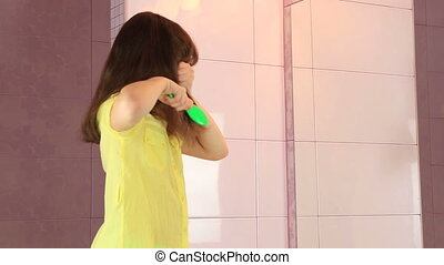 Beautiful little girl combing her hair before mirror.
