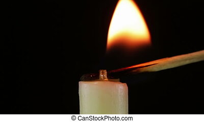 Burning Candle and Flame - Candle close-up on a black...