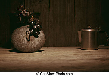 Coffee percolator, black grapes on wooden table, copy space.
