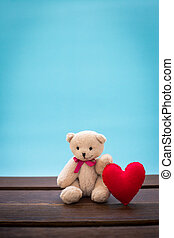 Teddy bear with pink heart decoration on wooden table over...