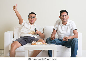 Men watching live sport game on tv at home