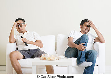 Men watching football match together - Men sitting on couch...