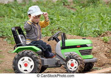 Young tractor driver - Young boy 2 years play in the garden...