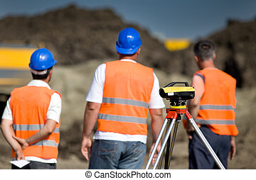 Theodolite and workers at construction site - Theodolite on...