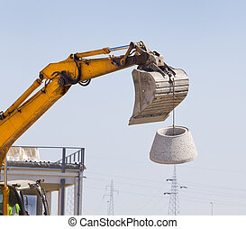Concrete manhole in the sky - Excavator bucket lifting...