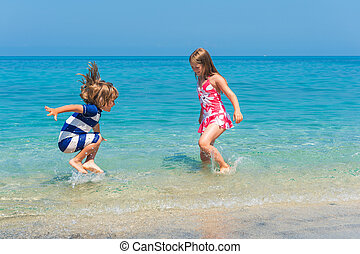 Two kids having fun on summer vacation, playing in the sea,...