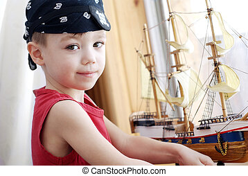 Pirate - Portrait of little pirate with model ship