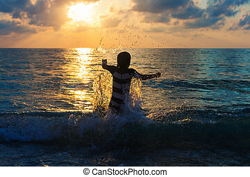 Adorable kid having fun on summer vacation at sunset,...