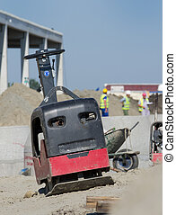 Vibratory plate compactor placed on sand slope at...