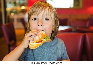 Boy eating big sandwich in cafe