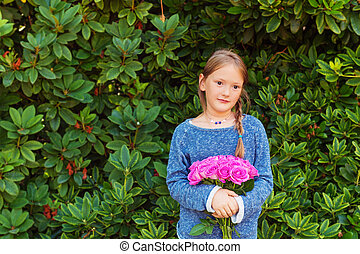 Outdoor portrait of adorable little girl of 7-8 years old,...