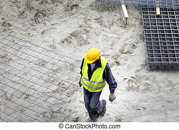 Construction worker carrying armature - Top view of...