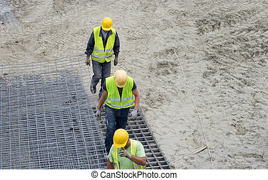 Construction workers carrying armature - Top view of...