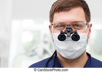 Attractive young dental doctor is working in his cabinet -...