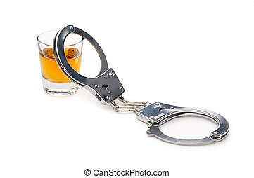 A drink and handcuffs, addiction or alcoholism