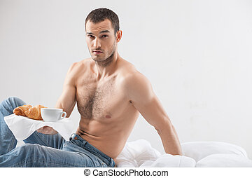 Attractive fit guy is serving food in bedroom - Portrait of...