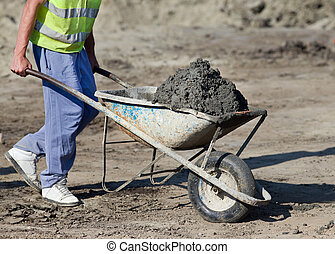 Construction barrow with concrete - Construction worker...