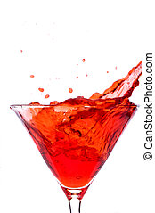 A cube od ice spalshing into a red martini alcoholic...