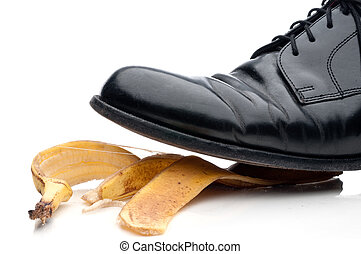Black leather business shoe about to slip on a bannana peel
