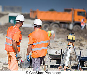 Construction workers - Two construction workers standing on...