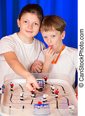 Boy and girl playing table hockey Children spend a hockey...