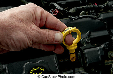 A mans hand pulling the dipstick to check the motor oil...