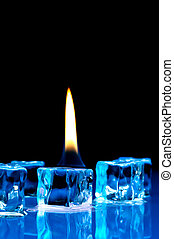Flame burning on blue ice cubes on a reflective surface -...