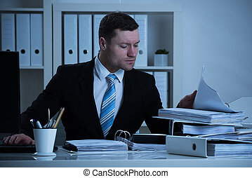 Businessman Working Late In Office - Mid adult businessman...