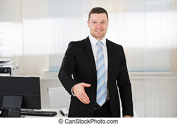 Happy Businessman Offering Handshake In Office