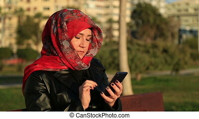 Muslim woman using smart phone - Arabic muslim woman wearing...