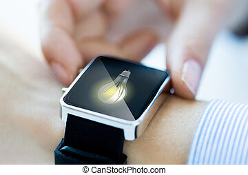 close up of hands with lightbulb on smartwatch - business,...