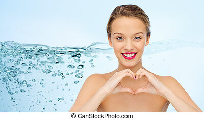 smiling young woman showing heart shape hand sign