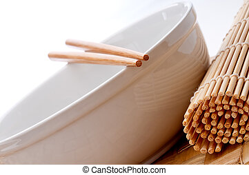 a tilted horizontal image of a pair of chopsticks on a white bowl with a sushi rolling mat on a weaved place-mat