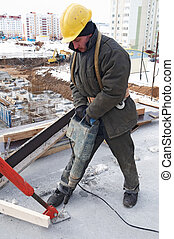 worker builder drill and concrete formwork