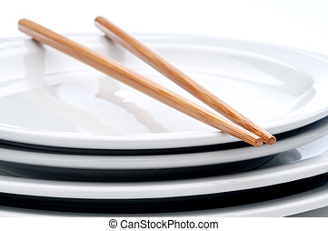 a horizontal close up of a pair of chopsticks on a stack of white plates